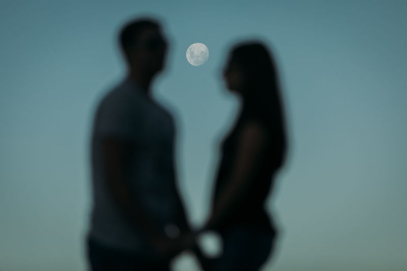 Silhouette of man and woman standing against blue background