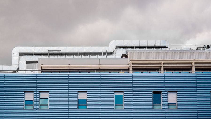 Low angle view of industrial building against cloudy sky