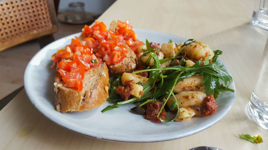 gnocchi salad and tomato buschetta on a white plate Food Food And Drink Freshness Ready-to-eat Plate Healthy Eating Gnocchi Rocket Tomato Bruschetta Baguette