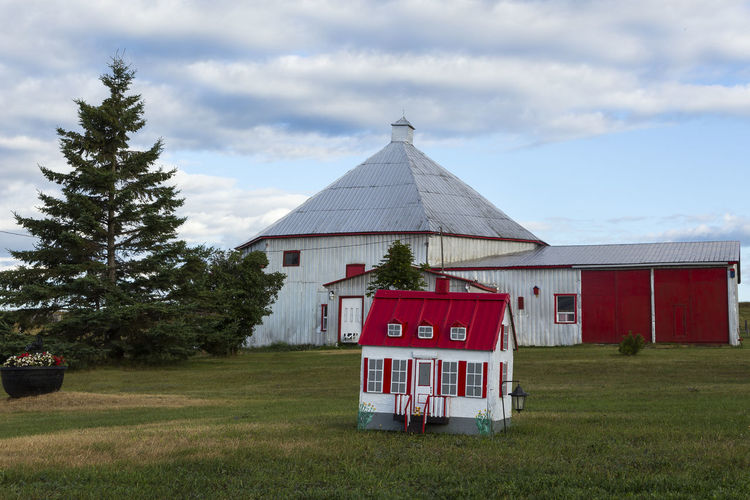 Vintage small decorative house with tin covered farm buildings in the background in Saint-Jean, Island of Orleans, Quebec Building Architecture Sky Cloud - Sky Small Decorative House Red And White Tin Roofs Farm Buildings Wooden Barn Saint-jean Island Of Orleans Québec Canada Rural Scene Tree Old Beautiful Summer Grass