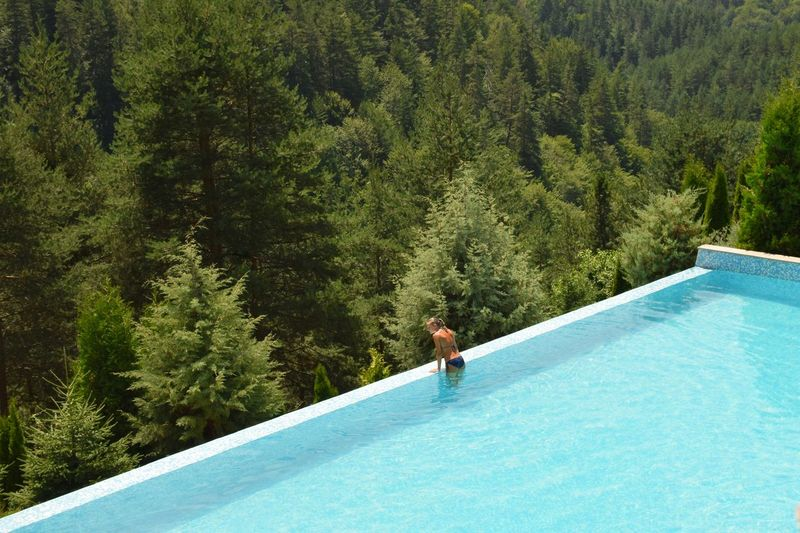 High angle view of young woman standing in swimming pool at forest