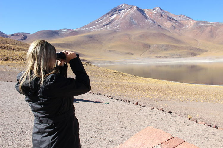 Woman looking through binoculars at desert