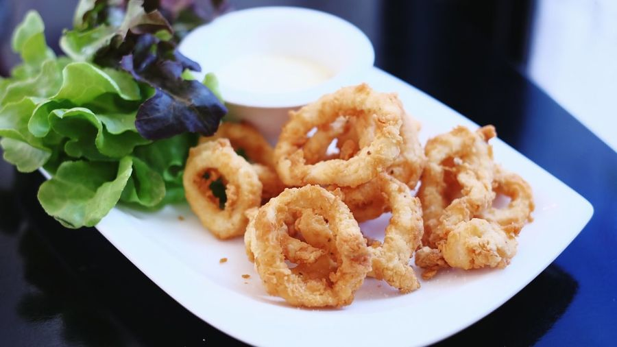 Close-up of served fried calamari fish in plate