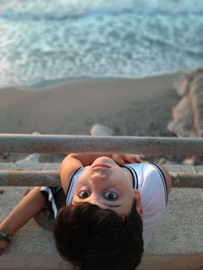 High angle portrait of boy relaxing on beach