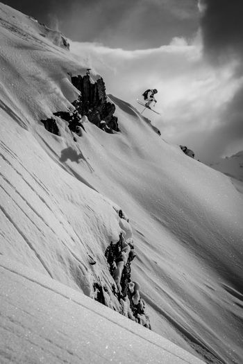 Side view of a skier jumping over snow covered slope