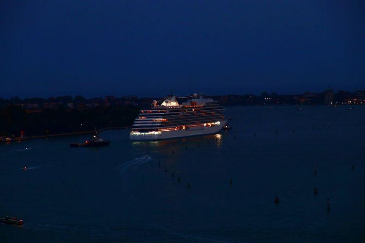 Illuminated ship in sea against sky at night