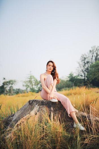 Portrait of young woman sitting on tree stump against clear sky