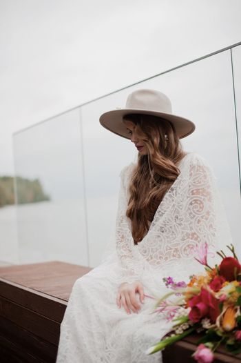 Bride sitting against glass railing