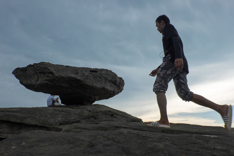 Side view of man standing on rock