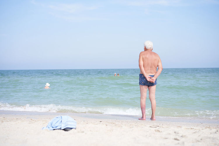 Rear view of shirtless man on beach against sky
