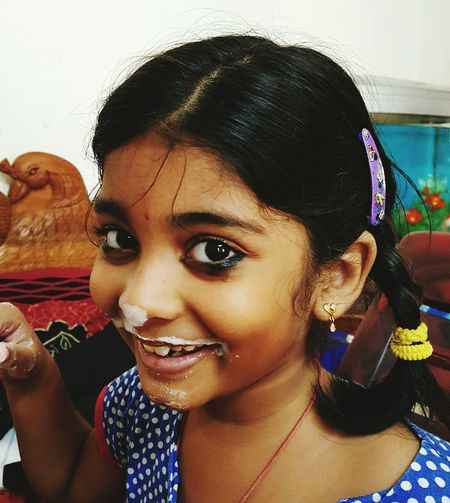 Close-up portrait of happy girl with curd on face