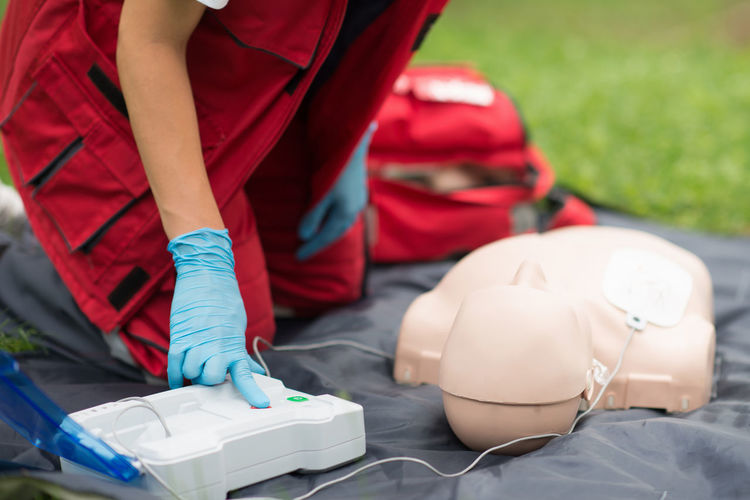 Midsection of paramedic practicing cpr on dummy