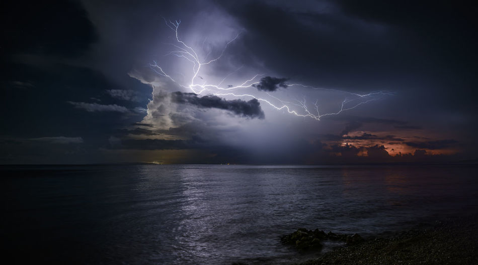 Lightning over sea against dramatic sky