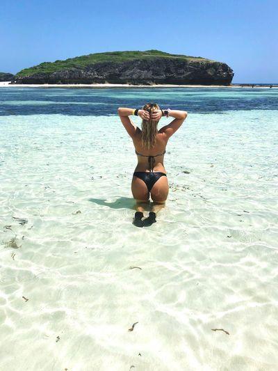 Rear view of woman kneeling in sea against clear sky