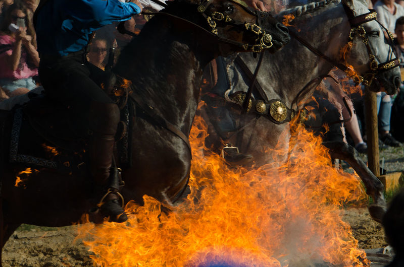 Low section of man jumping horse over fire during equestrian event