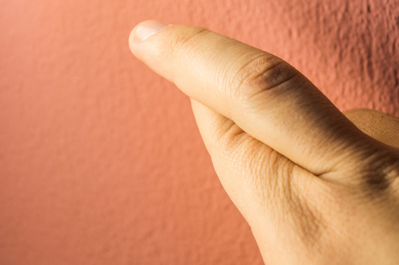 Close-up of hand against orange wall