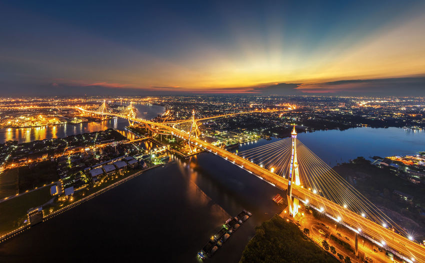 Illuminated bhumibol bridge over chao phraya river against sky during dusk