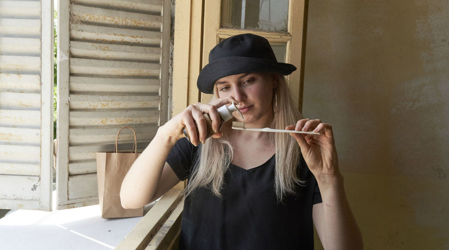 Portrait of young woman holding cigarette against wall