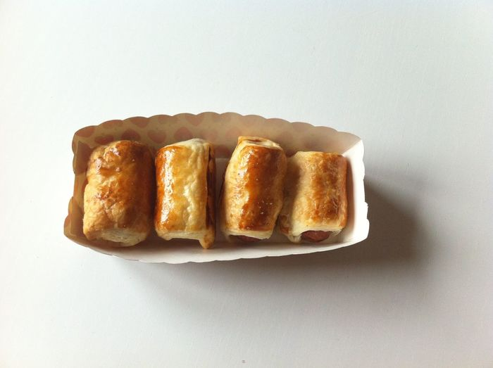 Sausage rolls in container on white background