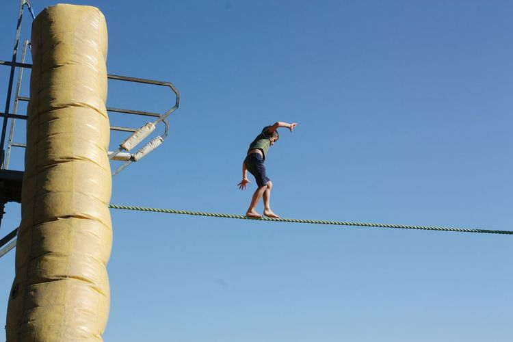 Low angle view of boy walking on rope against blue sky