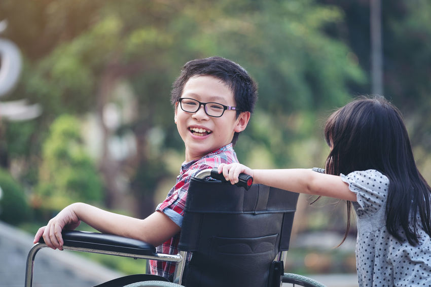 Happy boy in wheelchair with girl try drive a wheelchair of her brother smile, family time Brother Family Happy Sister WhellChair Boy Girl Smiling