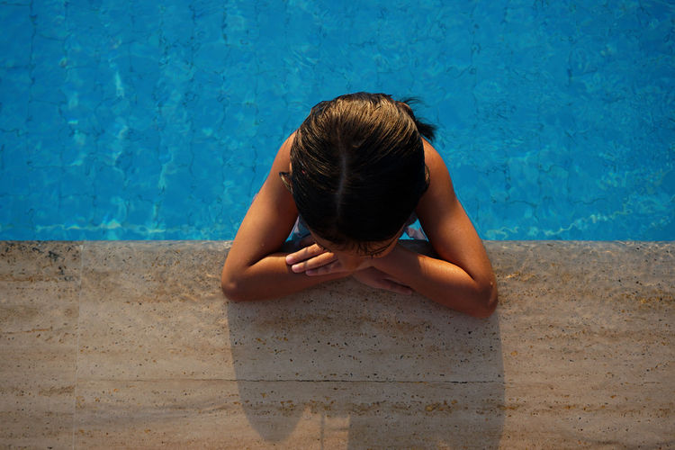 High angle view of girl relaxing in swimming pool