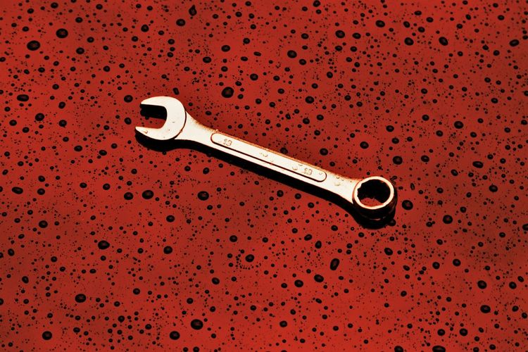 Close-up of wrench on red abstract background
