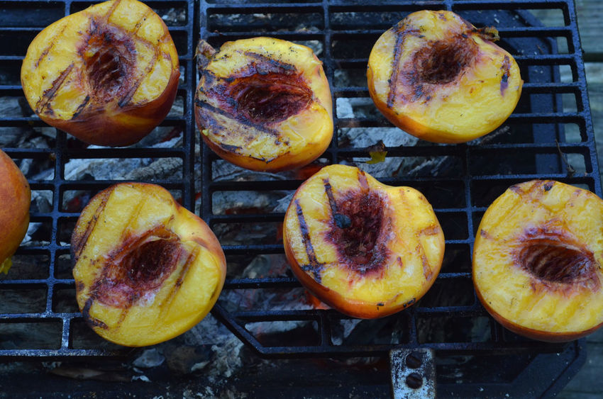 Peach halves grilling on top of a small tabletop Hibachi grill on picnic table outdoors Arrangement Close-up Dessert Extreme Close Up Freshness Grill Grilled Grilled Peaches Healthy Healthy Eating Healthy Food Hibachi Grill No People Peach Halves Ready-to-eat Sweet Food