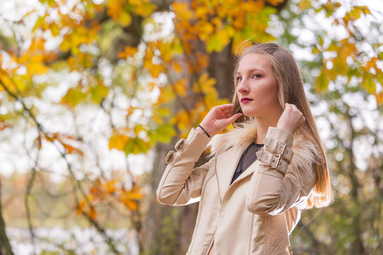 Beautiful woman holding her hair while standing at park during autumn
