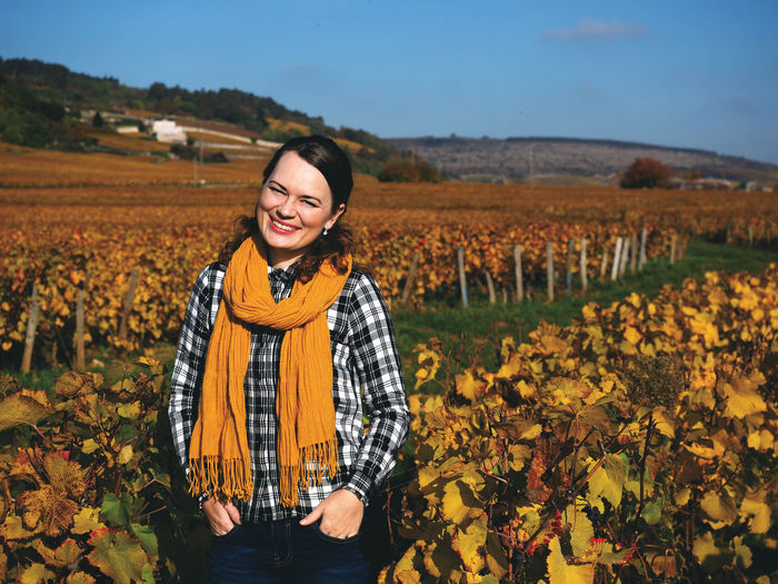 Portrait of smiling woman standing in vineyard
