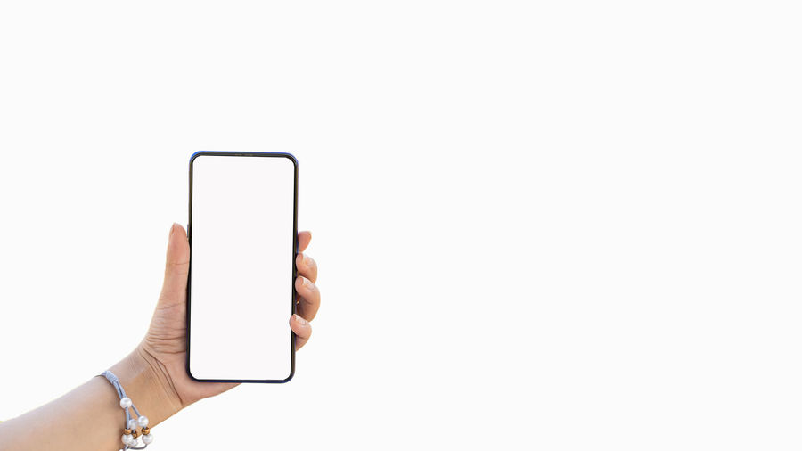 Hand holding smart phone against white background