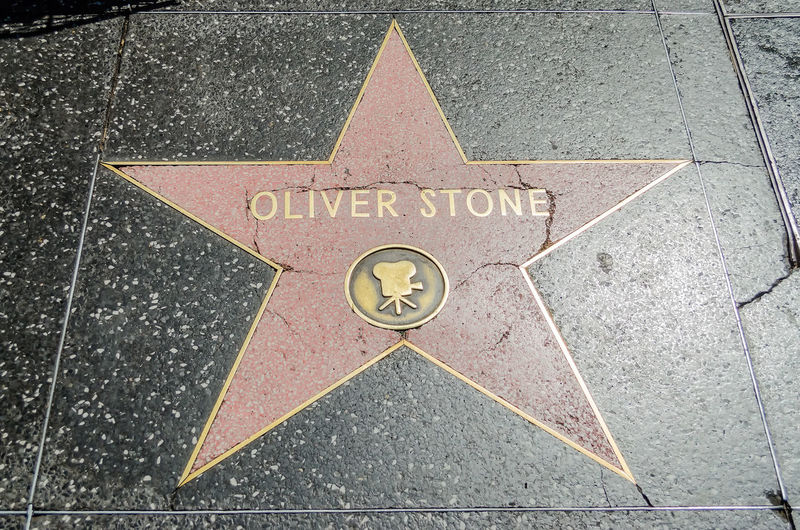 HOLLYWOOD - AUGUST 26, 2012: Oliver Stone's star on Hollywood Walk of Fame, as seen on August 26, 2012 in Hollywood in California. This star is located on Hollywood Blvd. and is one of 2400 celebrity stars. Arrow Arrow Symbol City Communication Day Direction Directional Sign Guidance High Angle View Information Information Sign No People Outdoors Road Road Sign Shape Sign Street Symbol Text Transportation Western Script