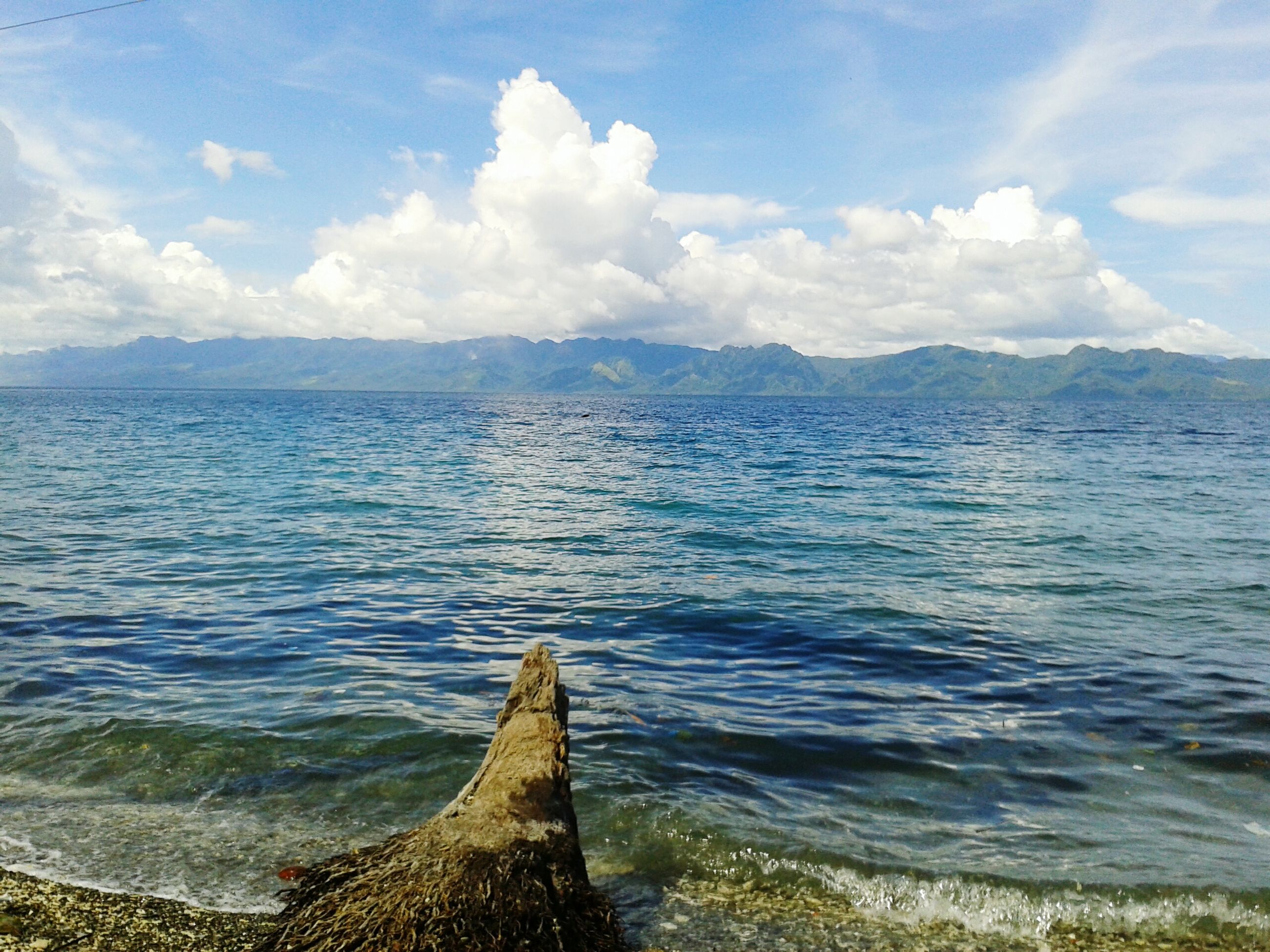 water, sea, sky, scenics, tranquil scene, beauty in nature, tranquility, nature, cloud - sky, mountain, rippled, idyllic, cloud, blue, horizon over water, day, non-urban scene, outdoors, remote, beach