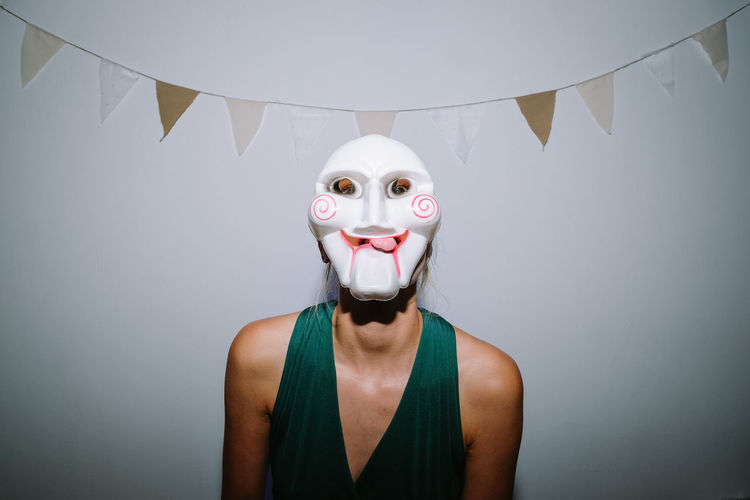 Portrait of person wearing mask standing against wall covered
