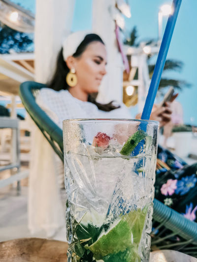 Selective focus of refreshing cocktail on table in bar and young woman in background.