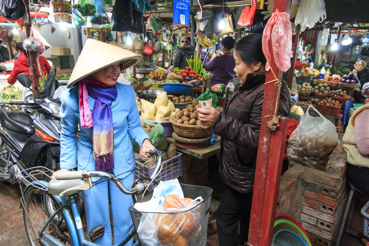 Hanoi, Vietnam - February 19, 2016: Woman buying vegetables on a local market in Hanoi, Vietnam ASIA Choice Collection Creativity Culture Day Food For Sale Hanging Out Hanoi, Vietnam Large Group Of Objects Man Made Object Market Mask - Disguise Outdoors People Person Retail  Side View South East Asia Street Variation