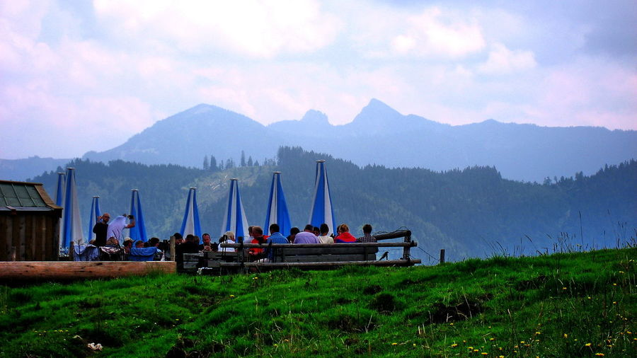 Alps Beer Garden Cloud - Sky Grass Landscape Leisure Activity Mountain Mountain Range Mountain View Nature Non-urban Scene People Person Scenics Sitting Sky Tourism The Essence Of Summer People And Places