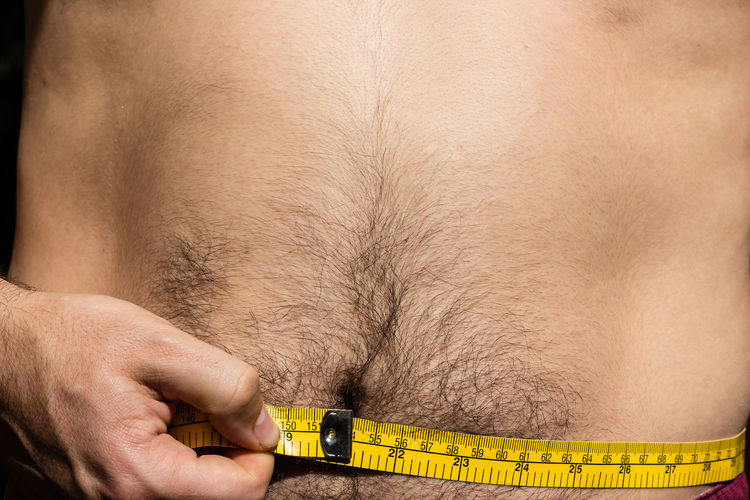 Midsection Of Man Measuring Abdomen