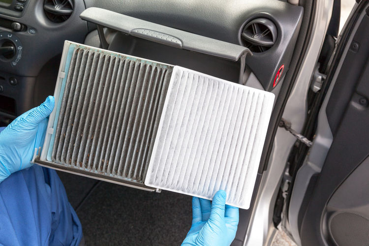 Auto mechanic, wearing protective blue gloves, holding clean and dirty car cabin air filters Close-up Holding Transportation Motor Vehicle Filter Air Air Filter Pollen Pollution Ventilation Service Hygiene Car Service Maintenance Auto Mechanic Airflow Cabin Dust Dusty Car Interior Allergen Auto Spare Part Replacing