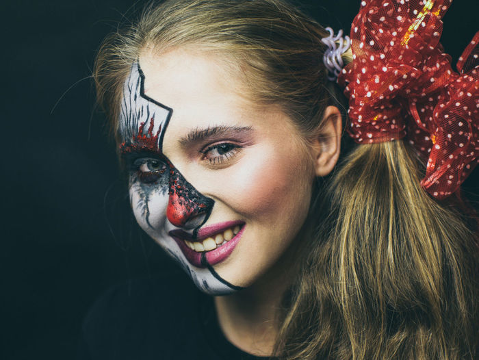 Close-up portrait of smiling woman with painted face against black background