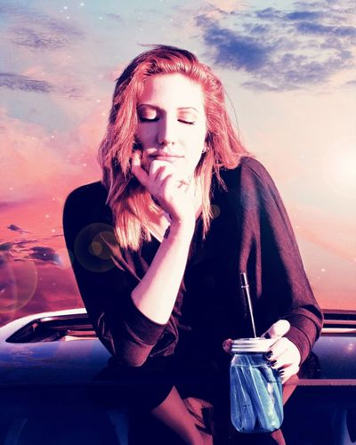Young woman holding drink on car roof against sky
