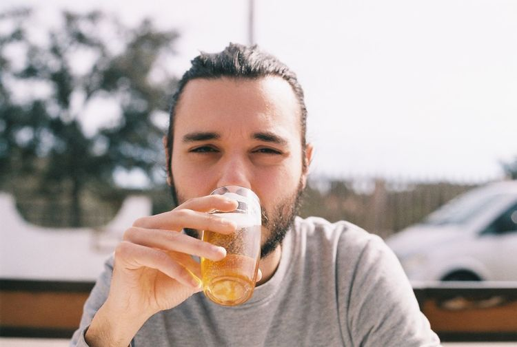 Portrait of young man drinking beer while sitting against sky