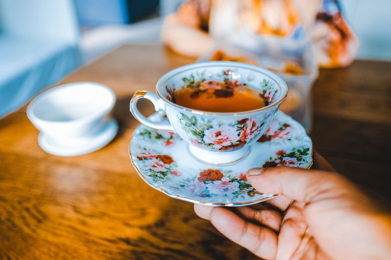 Close-up of person holding tea cup on table