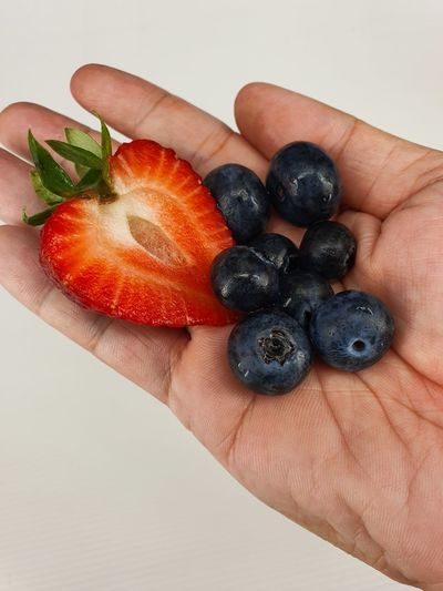 Close-up of hand holding strawberry over white background