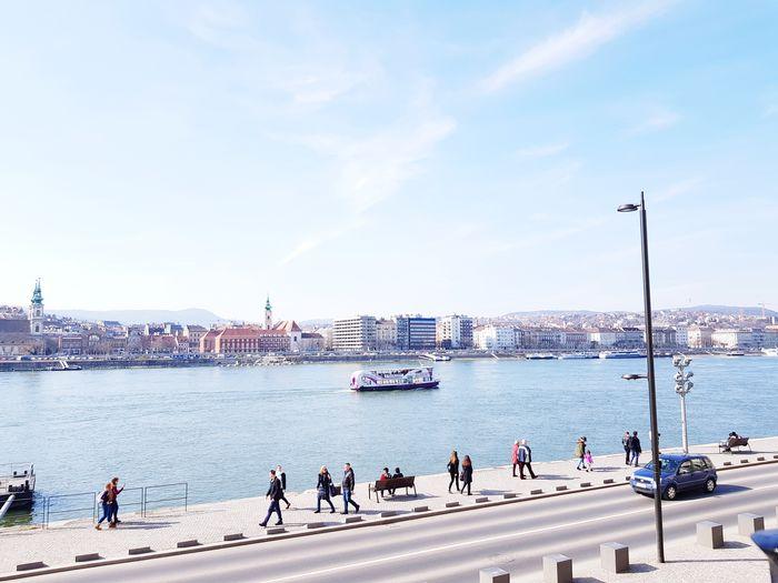 People walking on promenade by river in city against sky