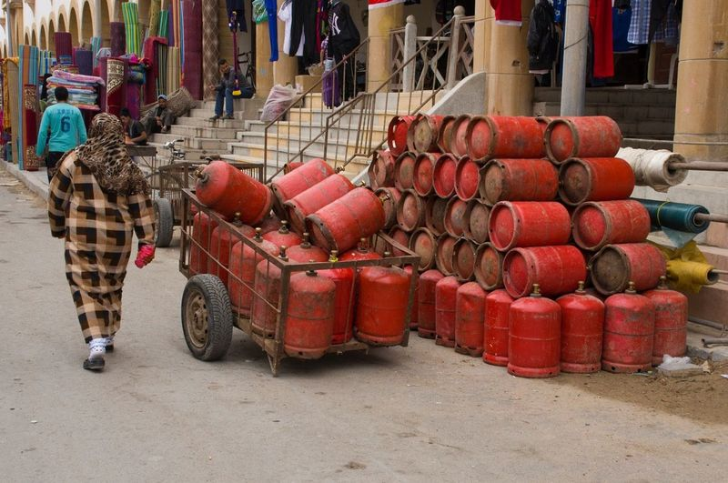Rear view of woman walking by red gas cylinders on street