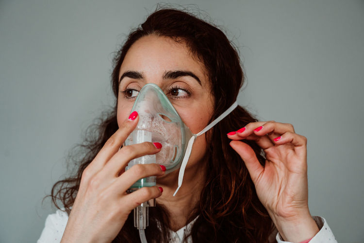 Woman wearing oxygen mask against gray background