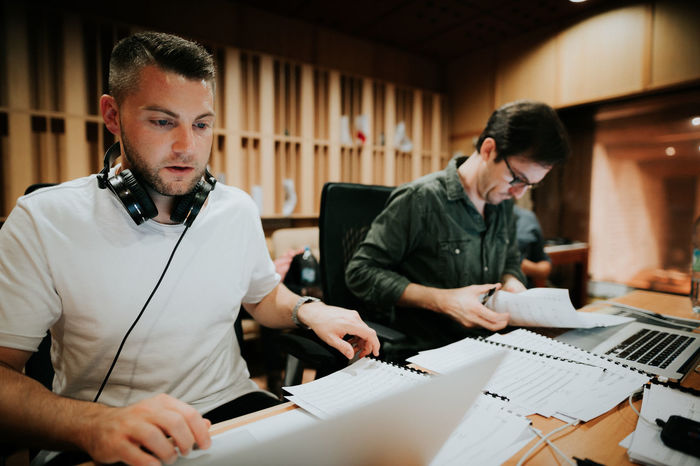 Sheet music Music Production Studio ARCHITECT Blueprint Casual Clothing Communication Composer Cooperation Design Professional Desk Indoors  Laptop Mid Adult Men Office Plan Standing Teamwork Technology Two People Waist Up Wireless Technology Working Young Adult Young Men