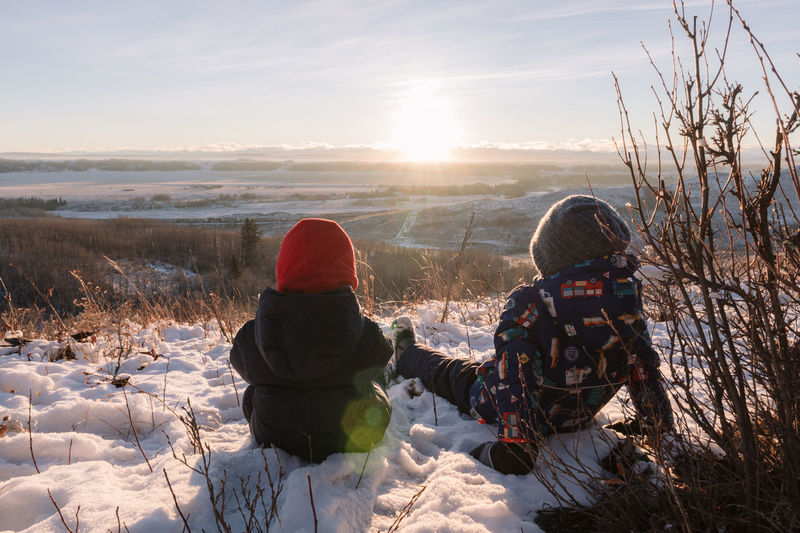 Scenic view of two boys sitting on the snow at sunset
