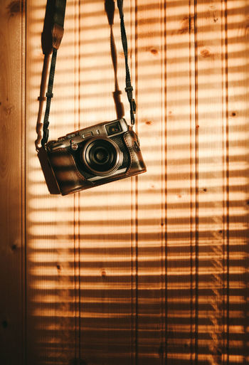 Close-up of camera hanging against wood